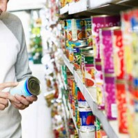 Man reading side of canned food in supermarket aisle